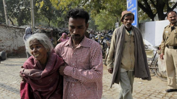 An unidentified relative of Ram Singh, the man accused of driving the bus on which the 23-year-old student was gang raped in December 2012, walks with Singh's mother as his father Mangelal, second right, follows behind outside the family's home in New Delhi, India, Monday, March 11, 2013. Indian police confirmed that Ram Singh, one of the men on trial for his alleged involvement in the gang rape and fatal beating of a woman aboard a New Delhi bus committed suicide in an Indian jail Monday, but his lawyer and family allege he was killed.(AP Photo/Manish Swarup) INDIA OUT