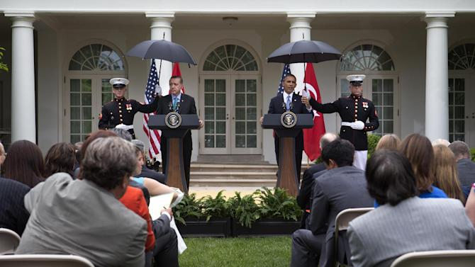 As Marines hold umbrellas during a light rain, President Barack Obama and Turkish Prime Minister Recep Tayyip Erdogan participate in a joint news conference in the Rose Garden of the White House in Washington, Thursday, May 16, 2013. (AP Photo/Jacquelyn Martin)