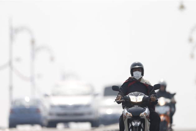 A motorist wears a face mask while travelling amid the haze in Muar