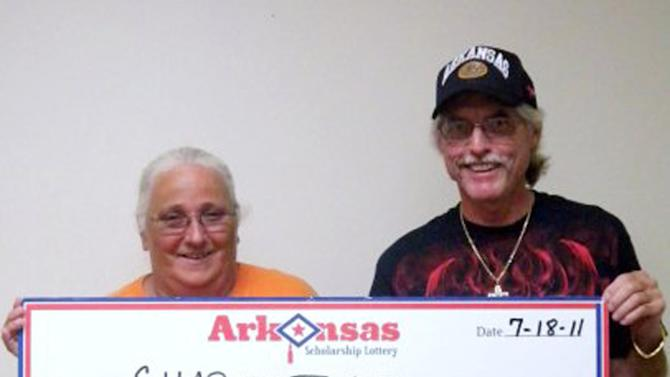 This photo provided by the Arkansas Scholarship Lottery shows Sharon Jones, left, and an unidentified man after Jones cashed the winning ticket in 2011. Jones may have to give up the winnings to a woman who threw away the ticket after she bought it, according to a judge's ruling Tuesday. (AP Photo/Arkansas Scholarship Lottery)