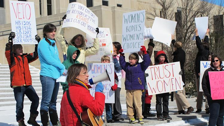 FILE - In this March 25, 2013, file photo Kris Kitko, left, leads chants of protest at an abortion-rights rally at the state Capitol in Bismarck, N.D. Abortion-rights advocates filed a lawsuit in federal court Tuesday, June 25, 2013, in Bismarck, N.D., challenging two new North Dakota laws that impose the nation's toughest abortion restrictions. (AP Photo/James MacPherson, File)