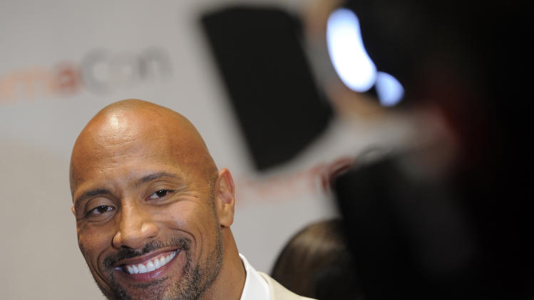 "FILE - Dwayne Johnson, a cast member in the upcoming film ""G.I. Joe: Retaliation,"" smiles during an interview on the opening night of CinemaCon 2012, the official convention of the National Association of Theater Owners, in this April 23, 2012 file photo. (AP Photo/Chris Pizzello, File)"
