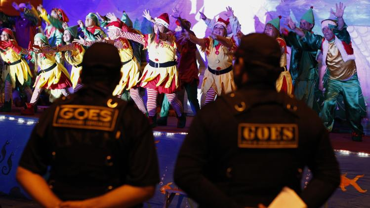 Prison guards watch a performance by inmates dressed as Santa's elves during an event ahead of Christmas celebrations at Santa Monica female prison in Lima