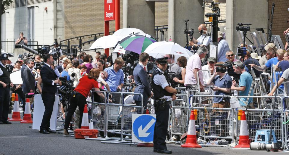 A British police officer stands near reporters outside St. Mary's Hospital exclusive Lindo Wing in London, Monday, July 22, 2013. Buckingham Palace officials say Prince William's wife, Kate, the Duchess of Cambridge, has been admitted to the hospital in the early stages of labor. (AP Photo/Lefteris Pitarakis)