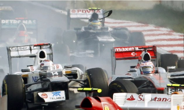 Sauber Formula One driver Kobayashi collides with McLaren Formula One driver Button on the first lap of the South Korean F1 Grand Prix at the Korea International Circuit in Yeongam