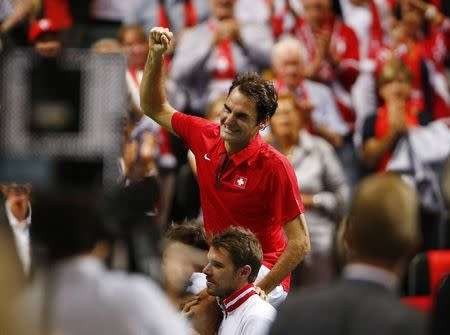 Federer celebrates on the shoulder of team members after winning his Davis Cup semi-final tennis match against Italy's Fognini at the Palexpo in Geneva