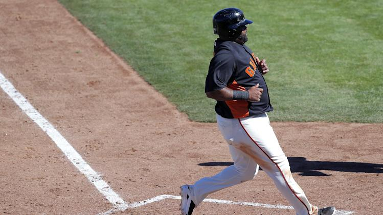 San Francisco Giants' Pablo Sandoval scores on a base hit by teammate Joaquin Arias during the third inning of a spring training baseball game against the Chicago White Sox, Monday, Feb. 25, 2013, in Scottsdale, Ariz. (AP Photo/Matt York)