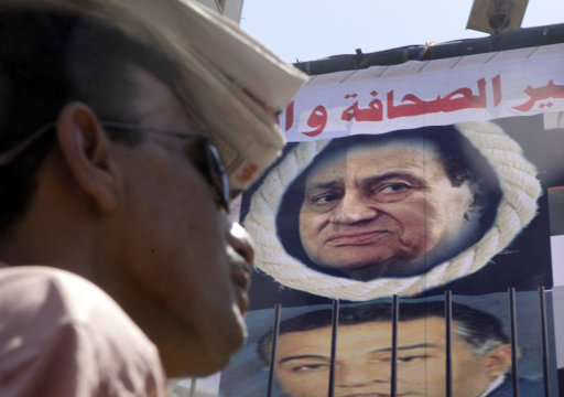 An Egyptian covers his head from the sun,  in front of a poster showing ousted Egyptian President Hosni Mubarak framed by a noose, during  Friday prayers at Tahrir Square, the focal point of Egyptian uprising, in Cairo, Egypt, Friday, July 8, 2011. Thousands of Egyptians took to the streets around the country Friday to demand justice for victims of Hosni Mubarak's regime and press the new, military rulers for a clear plan of transition to democracy. Arabic reads