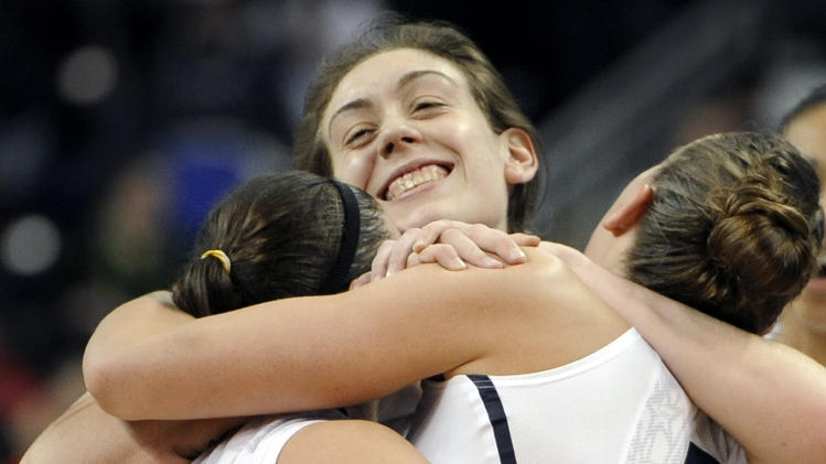 Connecticut's Breanna Stewart, center, embraces teammates Kelly Faris, left, and Heather Buck, right, at the end of a regional final game against Kentucky in the NCAA college basketball tournament in Bridgeport, Conn., Monday, April 1, 2013. Connecticut won 83-53.(AP Photo/Jessica Hill)
