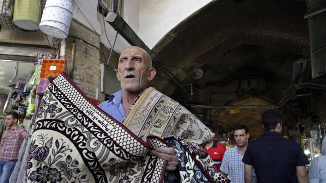 An Iranian man tries to sell carpets at the main entrance of the Tehran's old main bazaar in downtown Tehran, Iran, Sunday, Oct. 7, 2012. Iran's parliament on Sunday abandoned its planned impeachment of a Cabinet minister over the free-fall of the country's currency, opting instead to look for more effective economic measures, like cutting spending. The aborted move to impeach the minister reflects unease over the severe drop in the value of the Iranian rial, mostly because of Western sanctions over Iran's suspect nuclear program. On Sunday the parliament approved outlines of a bill to restrict the government's use of different exchange rates for its foreign revenue and requiring the return of some funds to the treasury. (AP Photo/Vahid Salemi)