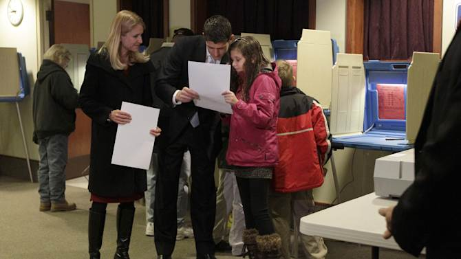 Republican vice presidential candidate, Rep. Paul Ryan, R-Wis., shows his ballot to his daughter Liza as his wife Janna looks on at left, while voting at the Hedberg Public Library in Janesville, Wis., Tuesday, Nov. 6, 2012.  (AP Photo/Mary Altaffer)