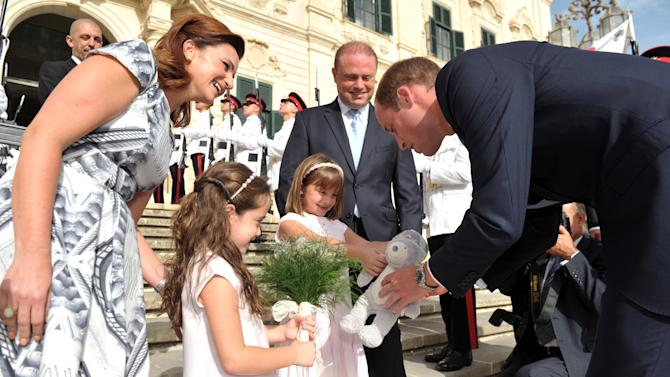 """In this photo released by the Maltese Department of Information, Prince William is welcomed by Malta's Prime Minister Joseph Muscat, background, his wife Michelle, left, and their two daughters at the office of the premier in Valletta, Malta, Saturday, Sept. 20, 2014. The Duke of Cambridge traveled without his wife because she is pregnant with her second child and """"continues to suffer from the effects of Hyperemesis Gravidarum"""", Kensington Palace said. (AP Photo/Reuben Piscopo, HO)"""