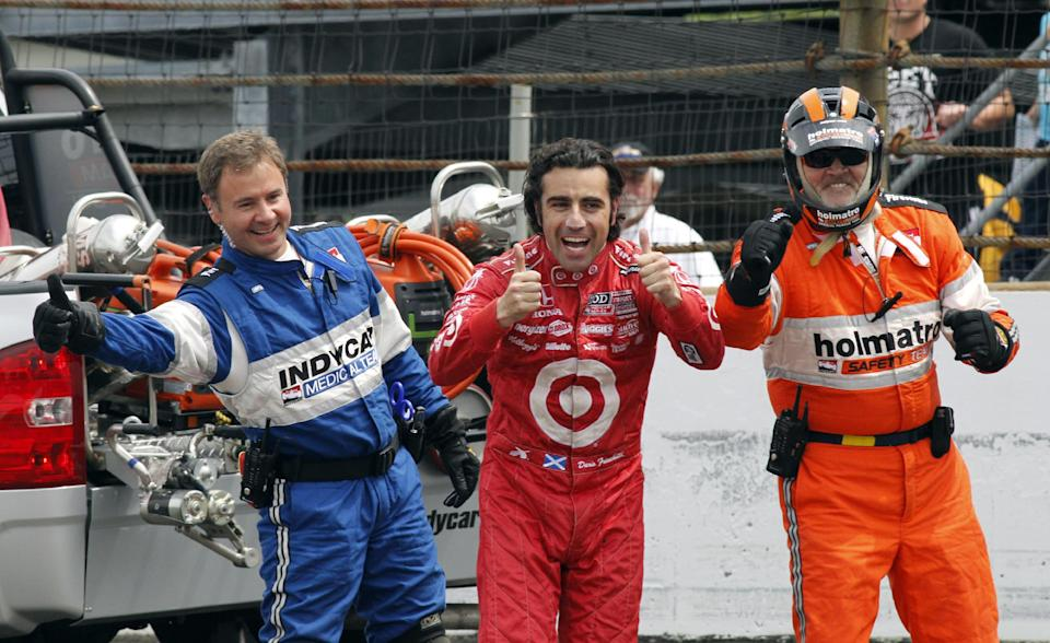 Dario Franchitti, center, of Scotland, along with safety team members, left and right, congratulate Tony Kanaan, of Brazil, who drives by under caution on his way winning the Indianapolis 500 auto race at Indianapolis Motor Speedway in Indianapolis, Sunday, May 26, 2013. (AP Photo/Tom Hemmer)