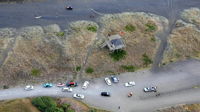 In this aerial photo, emergency vehicles are parked at Muriwai Beach near Auckland, New Zealand, Wednesday, Feb. 27, 2013, following a fatal shark attack. Police said a man was found dead in the water Wednesday afternoon after being