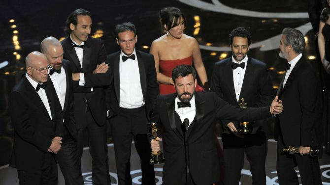 """Director/producer Ben Affleck, center, accepts the award for best picture for """"Argo,"""" as the cast and crew look on during the Oscars at the Dolby Theatre on Sunday Feb. 24, 2013, in Los Angeles.  (Photo by Chris Pizzello/Invision/AP)"""