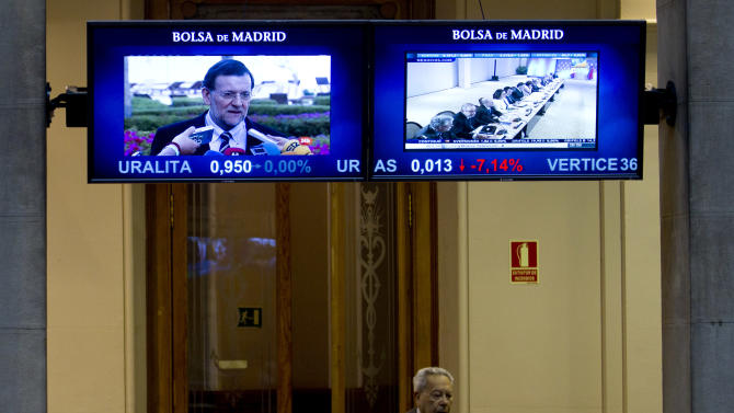 A broker walks through a door at the Stock Exchange as Spain's Prime Minister Mariano Rajoy appears on a screen in Madrid Monday June 18, 2012.  Spanish markets breathed a sigh of relief Monday with stocks opening higher and the country's borrowing costs dipping slightly after pro-bailout parties won the elections in Greece. Spain is a focus of fears it might be the next eurozone country to need a full bailout. The government is to announce this week how much of a euro100 billion fund it will tap to rescue banks that got burned when a real estate bubble popped. (AP Photo/Paul White)