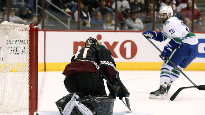 Vancouver Canucks' Chris Higgins (20) scores a goal against Arizona Coyotes' Mike Smith during the third period of an NHL hockey game Thursday, March 5, 2015, in Glendale, Ariz. The Coyotes defeated the Canucks 3-2 in a shootout. (AP Photo/Ross D. Franklin)