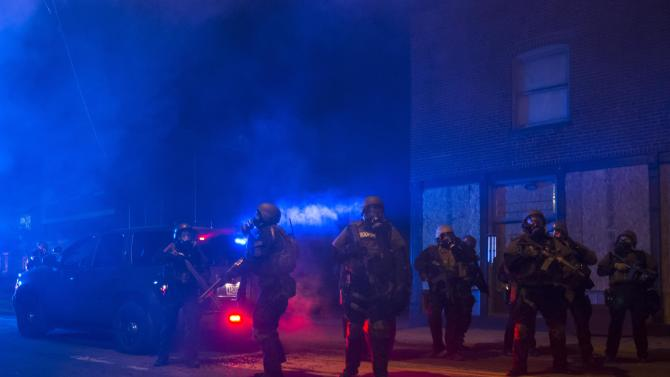 Police in riot gear stand guard after deploying tear gas to disperse protesters in Ferguson