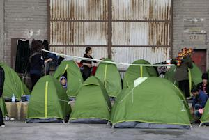 People sit outside their tents at the Athens' port …