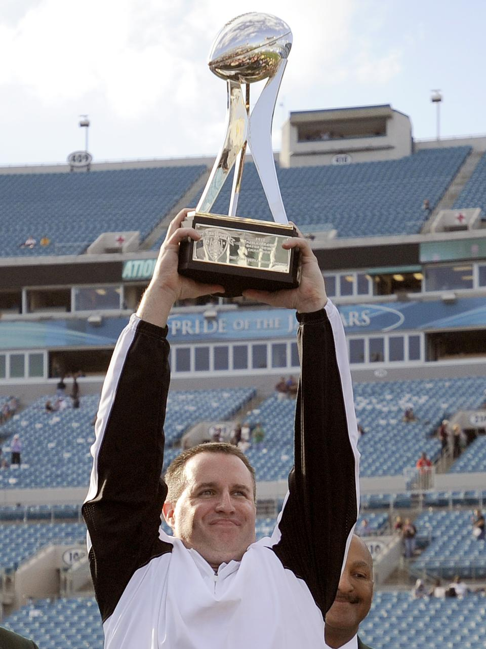 Northwestern head coach Pat Fitzgerald celebrates with the trophy after their 34-20 win over Mississippi State in the Gator Bowl NCAA college football game, Tuesday, Jan. 1, 2013 in Jacksonville, Fla.  (AP Photo/Stephen Morton)