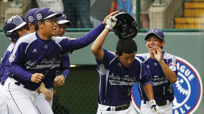 CORRECTS DATE AND YEAR TO AUG. 20, 2014 - Seoul's Jae Yeong Hwang, center, is greeted by teammates after hitting a solo home run off Tokyo pitcher Suguru Kanamori in the sixth inning of a International semi-final baseball game against Tokyo at the Little League World Series tournament in South Williamsport, Pa., Wednesday, Aug. 20, 2014