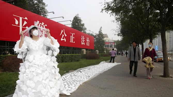 In this Oct. 20, 2014 photo, Chinese artist Kong Ning wears her 10-meter long wedding gown creation made of hundreds of face masks walks outside the Beijing Exhibition Center in Beijing, China. Kong created the gown hoping her act will call on more actions to fight the pollution which has shrouded the Chinese capital recently. (AP Photo) CHINA OUT