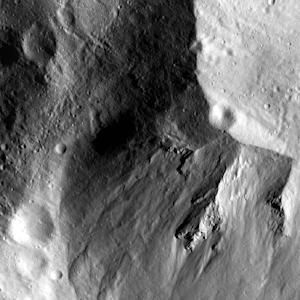 This undated image provided by NASA's Dawn spacecraft on Dec. 27,2011 showing a close-up view of a huge crater in the southern hemisphere of the Vesta asteroid. A recent analysis of images taken by the Dawn spacecraft reveals there are two overlapping craters in Vesta's south pole created by separate impact events. (AP Photo/NASA)