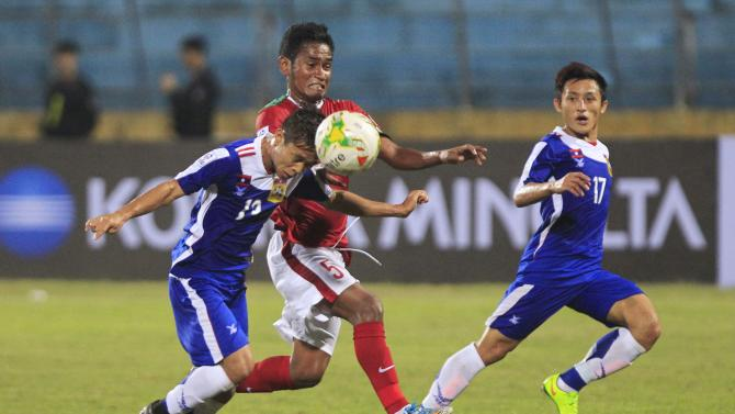 Indonesia's Rizki Ramdani Lestaluhu fights the ball with Laos' Bounthavy Sipasong and Vilayout Sayyabounsou in their Suzuki Cup Group A match at Hang Day Stadium in Hanoi