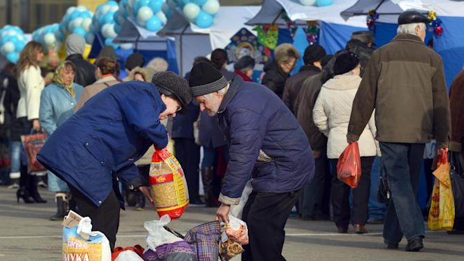 People buy foodstuff at a marketpalce in Russian southern city of Stavropol, on December19,2014