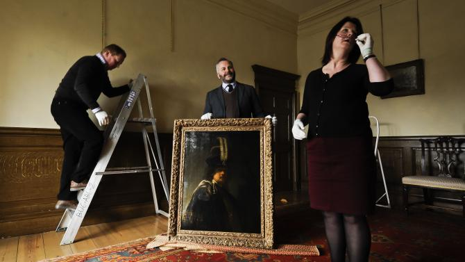 Buckland Abbey staff prepare to hang a recently confirmed self-portrait of Rembrandt, with Curator of Pictures and Sculpture David Taylor, centre, discovered at the Devonshire Abbey in Skipton, England, in this photo dated Wednesday March 13, 2013.  The masterpiece was gifted in 2010 to Britain's National Trust by the family estate of a wealthy property developer, and has now undergone detailed investigations led by the world's leading Rembrandt expert, Ernst van de Wetering, to determine its provenance before declaring it an original painting by the Dutch master.  The painting is now valued at 20 million pounds and will be hung at Buckland Abbey for a few months before being sent for cleaning and further expert analysis including x-ray and tree-ring dating of the beech panel it is painted on. (AP Photo/Ben Birchall, PA) UNITED KINGDOM OUT - NO SALES - NO ARCHIVES