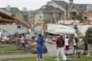 Neighbors view what remains of a home in Arlington, Texas, Tuesday April 3, 2012. Tornadoes tore through the Dallas area Tuesday, peeling roofs off homes, tossing big-rig trucks into the air and leaving flattened tractor trailers strewn along highways and parking lots. (AP Photo/The Fort Worth Star-Telegram, Ron Jenkins) MAGS OUT