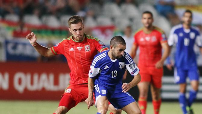 Cyprus' player Constantinos Charalambides (R) fights for the ball against Wales' player Aaron Ramsey during the EURO 2016 qualifying football match at the GSP stadium in the Cypriot capital Nicosia on September 3, 2015