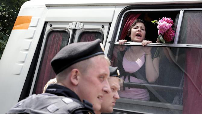 """Detained gay rights activists shout from a police bus near the State Duma, Russia's lower parliament chamber, in Moscow, Russia, Tuesday, June 11, 2013. Protesters attempted to rally outside the Russian State Duma before what is expected to be a final vote on the bill banning """"propaganda of nontraditional sexual relations."""" More than two dozen activists were detained in Moscow on Tuesday as they were protesting a bill that stigmatizes the gay community and bans the giving of information about homosexuality to children.  (AP Photo/Ivan Sekretarev)"""