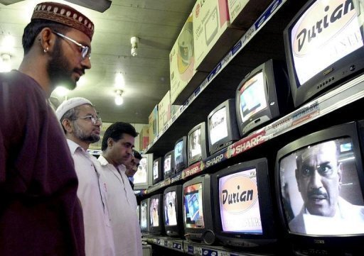 <p>People watch TV programes in Karachi. A Pakistani Hindu's conversion to Islam live on television during a prime-time Ramadan chat show has sparked criticism on behalf of religious minorities in the overwhelmingly Muslim country.</p>