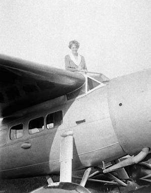 FILE - In this undated file photo, Amelia Earhart, the first woman to cross the Atlantic Ocean by plane sits on top of a plane. A Wyoming man who paid $1 million to sponsor a search for Amelia Earhart's missing airplane is asking a federal judge not to dismiss his fraud lawsuit against expedition organizers. Tim Mellon says the Pennsylvania-based International Group for Historic Aircraft Recovery and its executive director actually found Earhart's plane in 2010. Mellon, son of the late philanthropist Paul Mellon, claims the group kept the discovery secret it could keep seeking funds. (AP Photo,File)