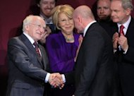 Newly elected Irish President Michael D Higgins (L) shales hands with his former rival Sean Gallagher (C) as Sinn Fein party's Martin McGuinness (R) looks on during the official announcement of the Irish presidential election's results at Dublin Castle in Dublin