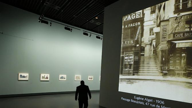 """A man walks by a Eugene Atget photography display as part of the retrospective for Edward Hopper, one of the great American 20th century artists at Paris' Grand Palais Museum, in Paris, Monday, Oct. 8, 2012.  This major Hopper retrospective reveals that the 20th century painter known for his rendering of American life, also drew inspiration from France, and includes some 128 Hopper works, such as the masterpieces """"Nighthawks"""" and """"Soir Bleu"""".(AP Photo/Francois Mori)"""