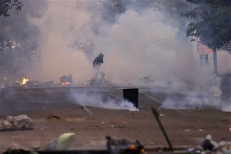 An anti-government protester runs through teargas during clashes in Caracas