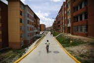 A boy rides a bicycle among apartment buildings in Ciudad Caribia outside Caracas September 19, 2013. REUTERS/Jorge Silva