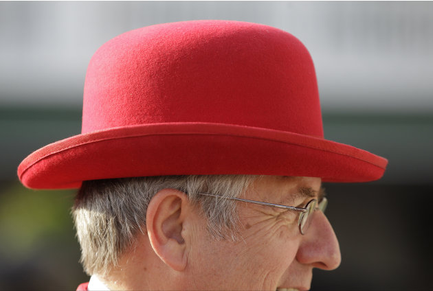 Jim Leuenberger, from Shawano, Wis., wears a red bowler hat white while walking through the paddock before the 138th Kentucky Derby horse race at Churchill Downs, Saturday, May 5, 2012, in Louisville,