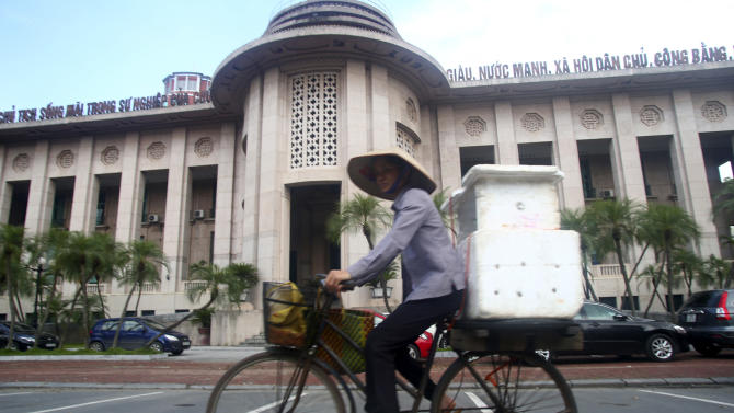 In this photo taken Sunday, Sept. 9, 2012, a street vendor cycles past the Central Bank of Vietnam in Hanoi, Vietnam. Once seen as an emerging Asian dynamo racing to catch up with its neighbors, Vietnam's economy is mired in malaise, dragged down by debt-hobbled banks, inefficient and corrupt state-owned enterprises and bouts of inflation. (AP Photo/Na Son Nguyen)
