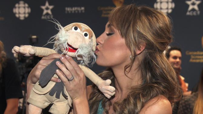 Actress Amber Marshall kisses a doll handed to her by a fan as she arrives at the 2015 Canadian Screen Awards in Toronto