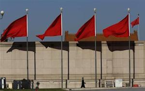 A Paramilitary soldier walks underneath red flags on the Tiananmen square next to the Great Hall of the People where the Chinese Communist Party plenum is being held in Beijing