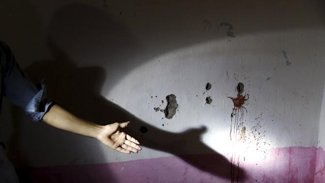 A man shows the bullet holes on the wall of a house after a shoot out between police and militants in Peshawar