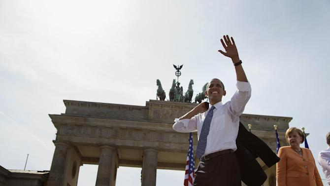 President Barack Obama, accompanied by German Chancellor Angela Merkel, waves to the crowd after speaking at the Brandenburg Gate in Berlin, Wednesday, June 19, 2013. Obama called to reduce the world's nuclear stockpiles, including a proposed one-third reduction in U.S. and Russian arsenals. (AP Photo/Evan Vucci)