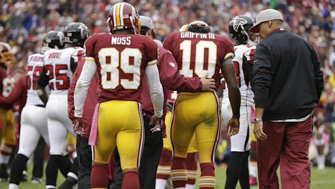 Washington Redskins quarterback Robert Griffin III walks off the field after being hit by Atlanta Falcons defensive end Jonathan Massaquoi during the second half of an NFL football game in Landover, Md., Sunday, Oct. 7, 2012. (AP Photo/Evan Vucci)