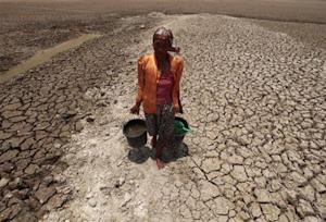 Female villager walks after collecting water from the base of a dried-up reservoir, due to the long dry season, at Kedung Sumber village