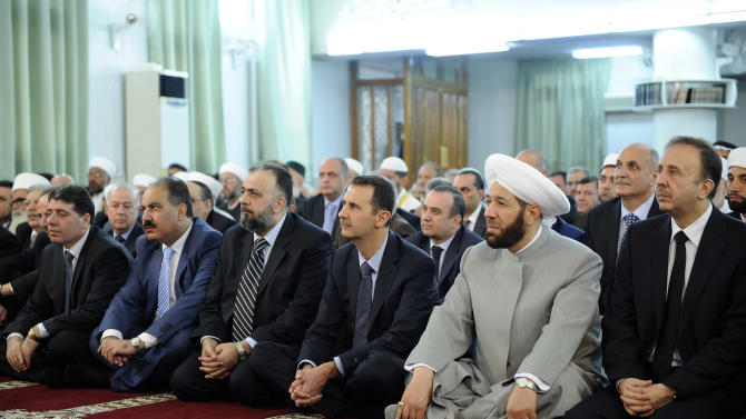 In this photo released by the Syrian official news agency SANA, President Bashar Assad, third right in front row, alongside Syria's grand mufti, second right, prays at the start of Eid al-Fitr, the three-day holiday that ends the holy month of Ramadan at the Anas bin Malik Mosque, Damascus, Syria, Thursday Aug. 8, 2013. Mortar rounds on Thursday hit an upscale district of Damascus where Assad attended prayers to mark the start of a major Muslim holiday in a rare attack in the high security area. (AP Photo/SANA)