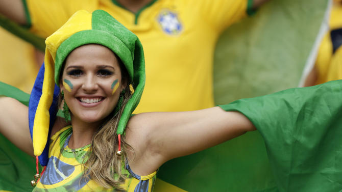 A Brazilian fan poses with her national flag before the group A World Cup soccer match between Brazil and Mexico at the Arena Castelao in Fortaleza, Brazil, Tuesday, June 17, 2014. (AP Photo/Marcio Jose Sanchez)