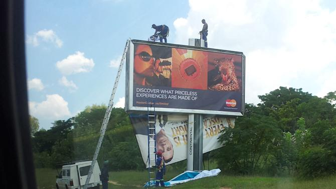 Photo taken through a car window shows workers taking down a billboard of Olympic athlete Oscar Pistorius endorsing a product in Johannesburg, Thursday, Feb. 14, 2013.  Pistorius was taken into custody after a 30-year-old woman, Reeva Steenkamp, was shot dead at his home. Front billboard for Master Card has nothing to do with Pistorius story.  (AP Photo/Dion Chang)